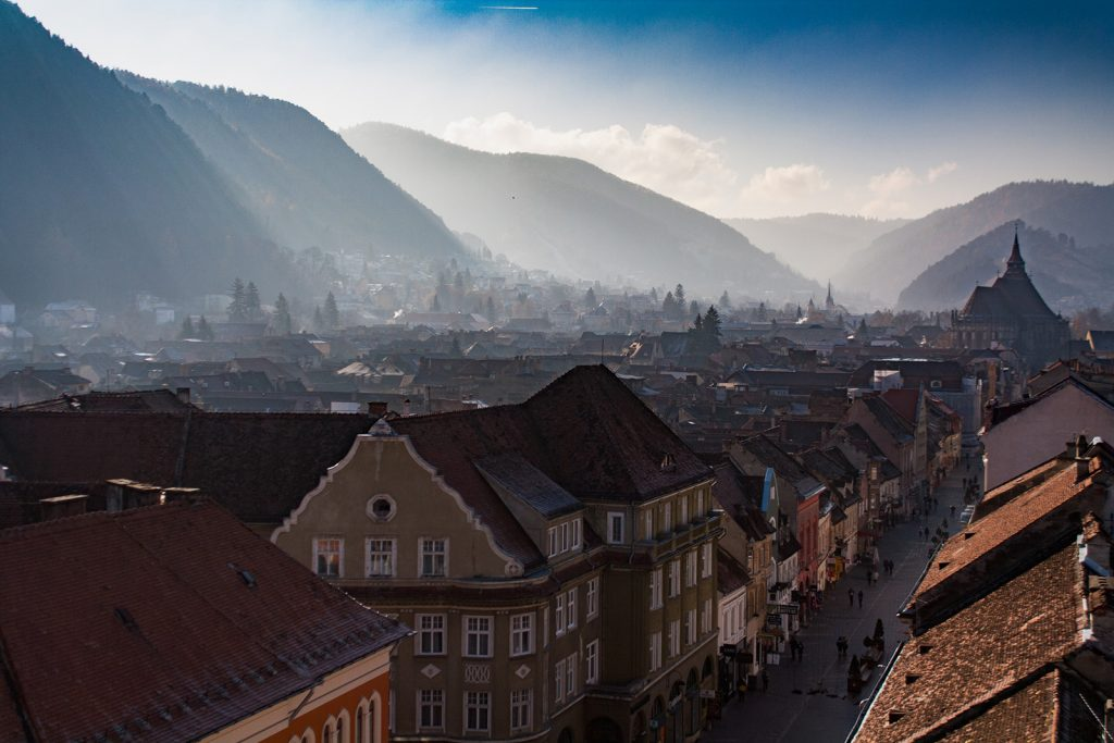 City view of Brasov old city center with hills and the Black Church in the background