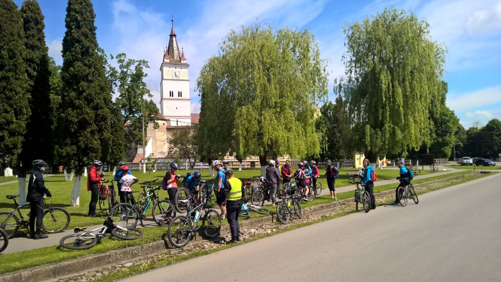 Cyclists in front of the fortified church in Harman, Brasov, Romania