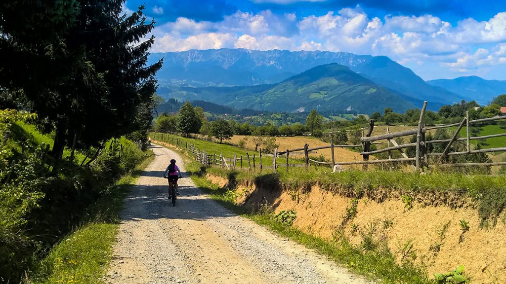 Cycling on a gravel road from Rasnov to Bran, overlooking the Piatra Craiului mountains in Brasov, Romania