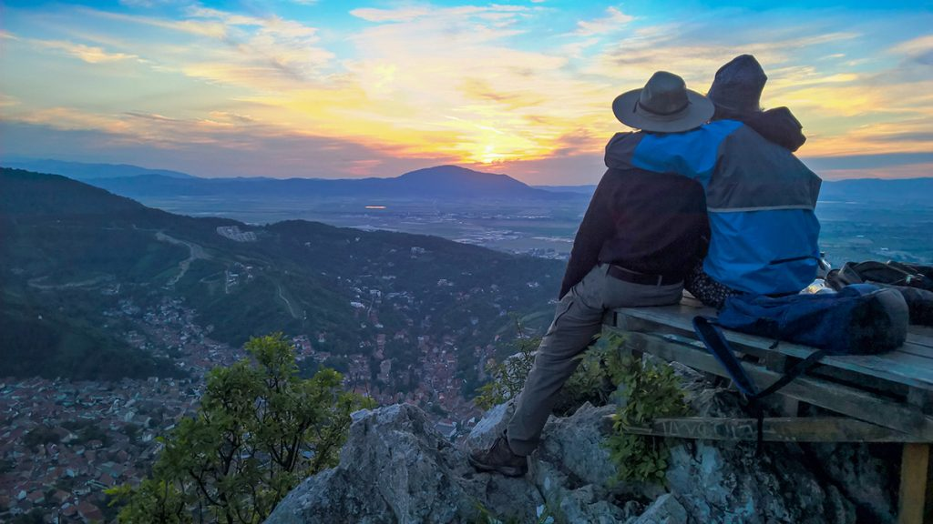 A couple looking at the sunset from mount Tampa, in Brasov, Romania